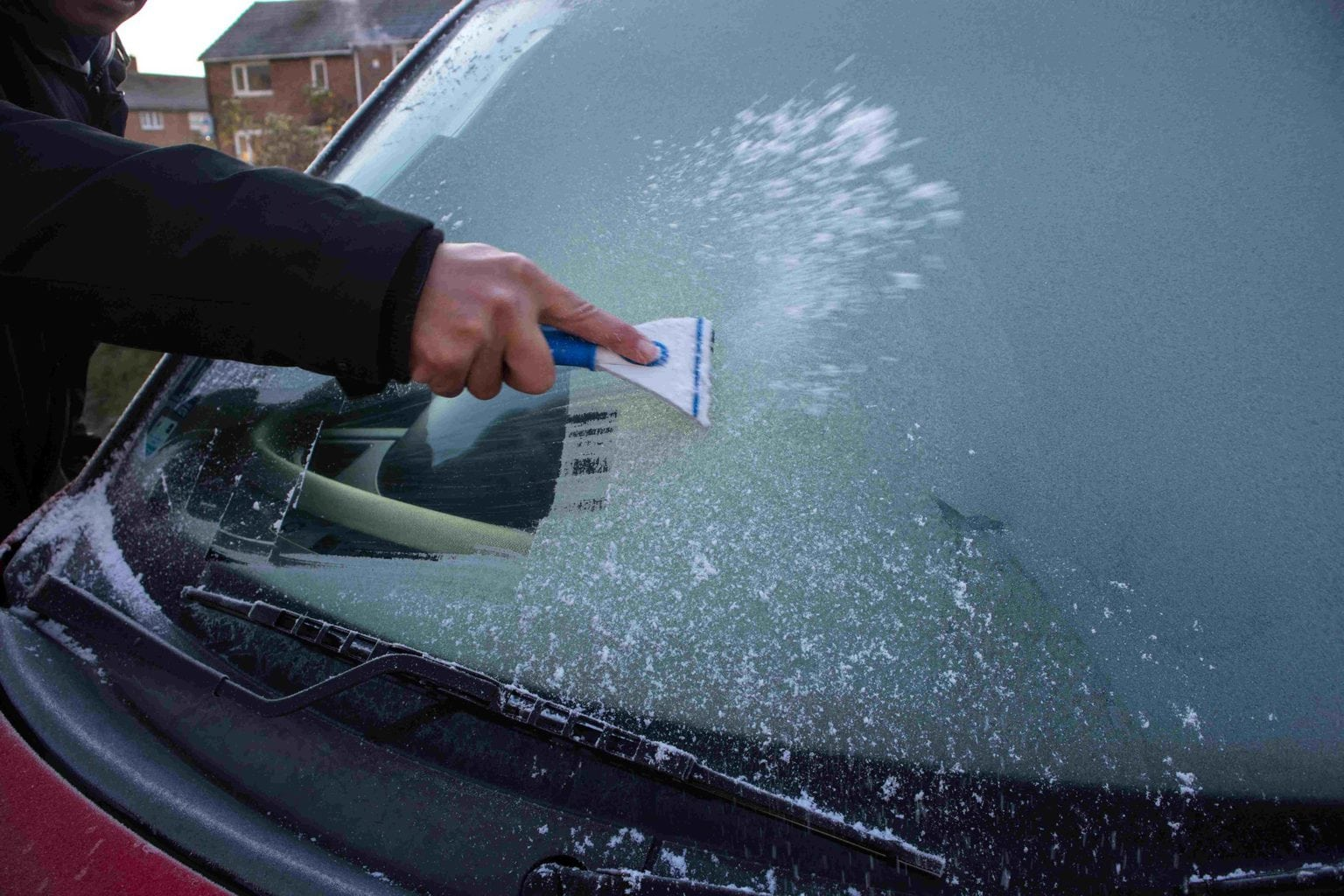 De-icing the windscreen of a car. This is an important winter driving safety tip for employees.